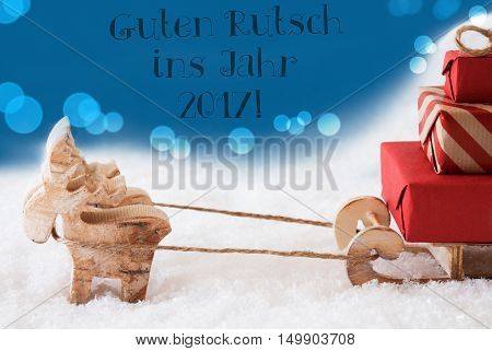 Moose Is Drawing A Sled With Red Gifts Or Presents In Snow. Christmas Card For Seasons Greetings. Blue Background With Bokeh Effect. German Text Guten Rutsch Ins Jahr 2017 Means Happy New Year