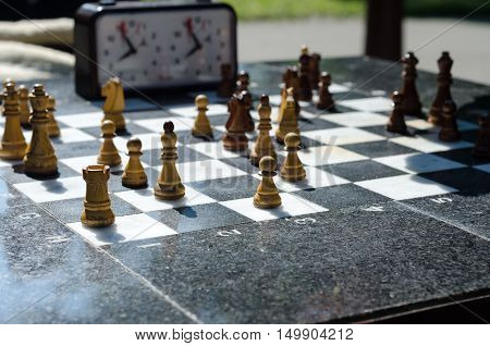 Stone chessboard with wooden chess on it.