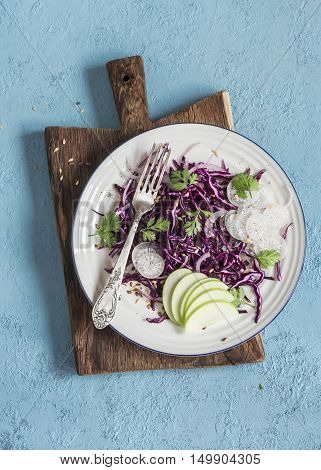 Red cabbage and apple slaw. Tasty vegetarian diet food. On a blue background top view