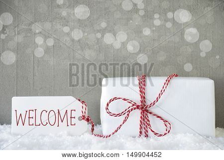 One Christmas Gift Or Present On Snow. Cement Wall As Background With Bokeh. Modern And Urban Style. Card For Birthday Or Seasons Greetings. Label With English Text Welcome