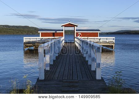 GREAT-LAKE, SWEDEN ON JULY 05. View of a bridge on July 05, 2016 by the Great-Lake, Sweden. Red and white wooden bridge, forest and ridges in the background. Editorial use.