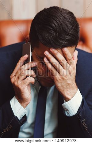 Depressed businessman talking on phone. Man holding palm on face being shocked of information. Failure, bankruptcy concept. Unsuccessful negotiations.