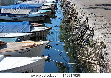 Covered small sea boats docked with multiple ropes