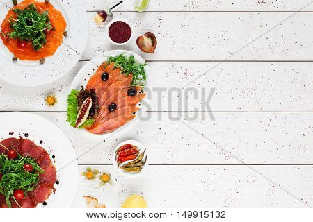 Plates with smoked fish and meat, free space. Appetizing snacks on white wooden background, flat lay, copy space for text