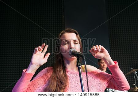 Attractive emotionally woman singing lyric song, free space. Close-up portrait of beautiful female soloist with microphone on stage.