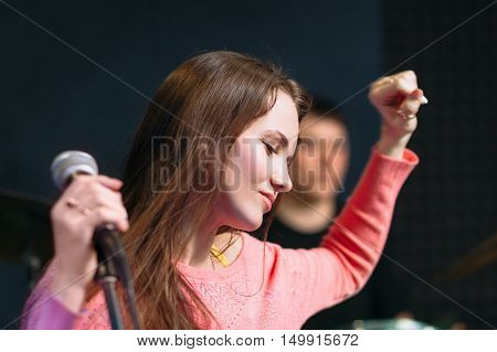 Young woman feeling drive on performance. Female soloist enjoying band playing while she standing near microphone. Joy, fun, leisure concept