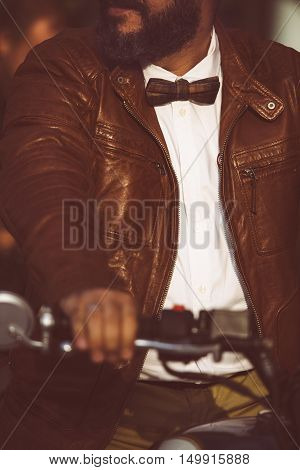 Close-up of unrecognizable bearded man in bowtie and leather jacket sitting on motorbike with arm on handle