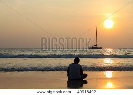A girl sitting by the sea at sunset and looking at a passing boat in a light summer dress. She looks at the sea. Sun sets over the horizon.
