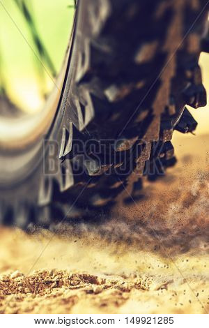 Mountain bike wheel close up with dirt dust particles MTB bicycle ride through sandy ground