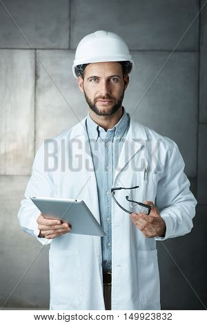 Portrait of confident young engineer wearing protective hardhat using ipad tablet.