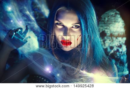 Beautiful Halloween Vampire Woman portrait. Beauty Angry Sexy Vampire Witch lady with blood on mouth posing in crypt, wearing spider web. Art design. Mysterious Model girl with Halloween make up