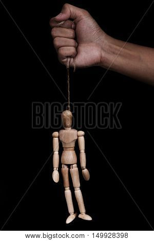 Hand holding rope with wooden puppet marionette hangman, low key image,on black background