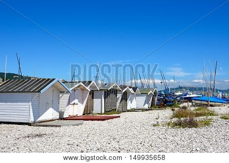 LYME REGIS, UNITED KINGDOM - JULY 18, 2016 - Huts on the pebbly beach with yachts to the rear Lyme Regis Dorset England UK Western Europe, July 18, 2016.