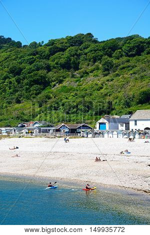 LYME REGIS, UNITED KINGDOM - JULY 18, 2016 - Holidaymakers relaxing on the beach with beach huts and town buildings to the rear and canoeists in the foreground Lyme Regis Dorset England UK Western Europe, July 18, 2016.