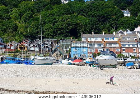 LYME REGIS, UNITED KINGDOM - JULY 18, 2016 - Yachts moored alongside the shingle beach with town buildings to the rear Lyme Regis Dorset England UK Western Europe, July 18, 2016.
