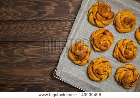 Homemade cinnamon buns with pumpkin over wooden background