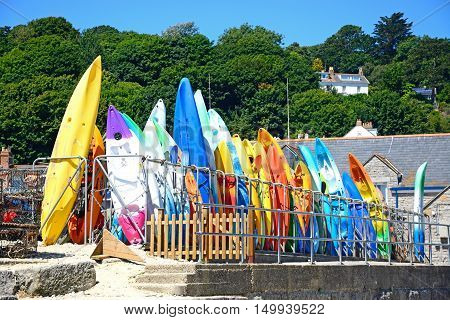 LYME REGIS, UNITED KINGDOM - JULY 18, 2016 - Colourful canoes stacked on the harbour wall Lyme Regis Dorset England UK Western Europe, July 18, 2016.