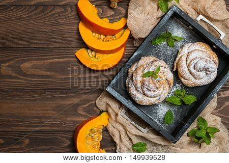Homemade cinnamon buns with pumpkin over wooden background, top view