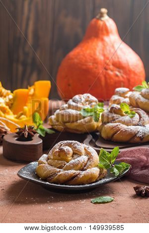 Homemade cinnamon buns with pumpkin over brown background,