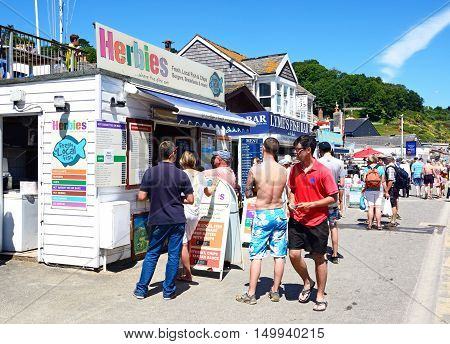 LYME REGIS, UNITED KINGDOM - JULY 18, 2016 - Tourists queuing to buy fish and chips from a beachfront chip shop Lyme Regis Dorset England UK Western Europe, July 18, 2016.