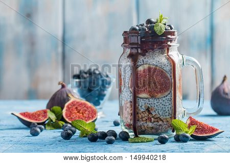 Glass jar of healthy breakfast with muesli, pudding with chia seeds, fresh fig and berries on blue background