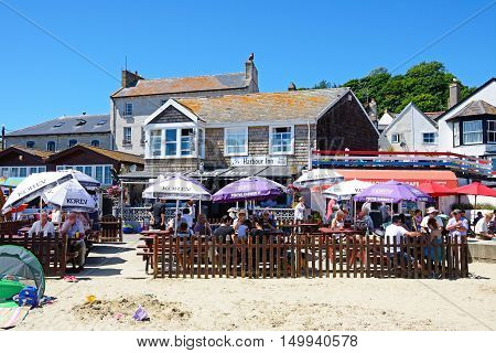LYME REGIS, UNITED KINGDOM - JULY 18, 2016 - Tourists relaxing at a beach cafe with the Harbour Inn pub to the rear Lyme Regis Dorset England UK Western Europe, July 18, 2016.