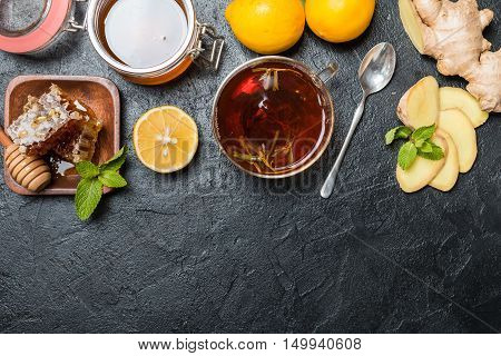 Cup of ginger tea with lemon and honey on slate background, top view with copy space