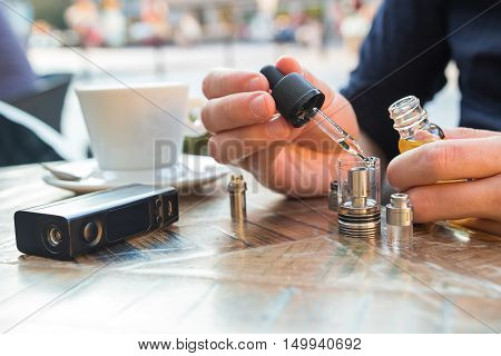 Man Filling An Electronic Cigarette Or Vaporizer With E-liquid