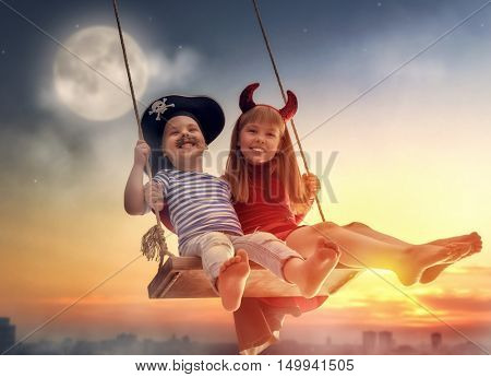 Two happy children on Halloween. Funny kids in carnival costumes outdoors. Cheerful boy and girl on swings on sunset background.