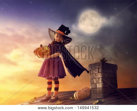 Happy Halloween! Cute little witch with a pumpkin. Beautiful young child girl in witch costume sitting on the roof.
