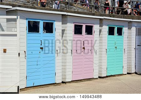 LYME REGIS, UNITED KINGDOM - JULY 18, 2016 - Row of colourful beach huts along the edge of the beach and promenade Lyme Regis Dorset England UK Western Europe, July 18, 2016.