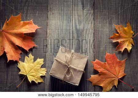 cardboard box tied with string on a bow on a wooden background in autumn leaves, holiday gift on Thanksgiving Hellouin. view from the top. copy space