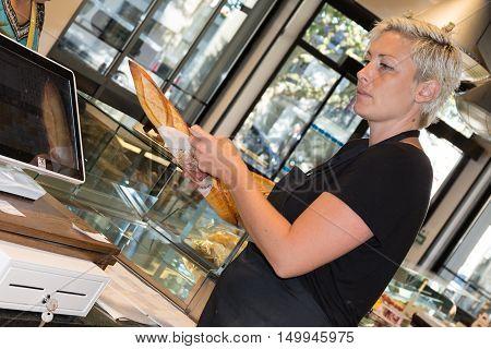 Female baker or saleswoman in her bakery selling fresh bread
