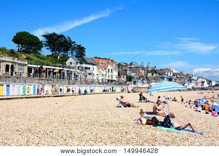 LYME REGIS, UNITED KINGDOM - JULY 18, 2016 - Holidaymakers relaxing on the pebble beach with the promenade and beach huts to the rear Lyme Regis Dorset England UK Western Europe, July 18, 2016.