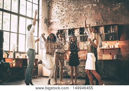 Just having fun. Full length of cheerful young people throwing confetti and jumping while enjoying home party on the kitchen