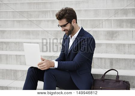 Smiling businessman with glasses using laptop on steps