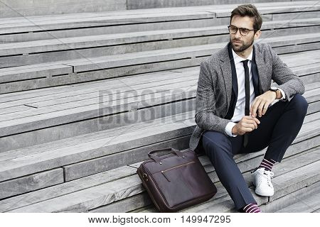 Businessman with glasses sitting on steps looking away