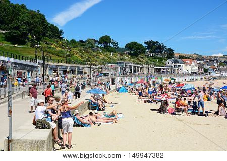 LYME REGIS, UNITED KINGDOM - JULY 18, 2016 - Holidaymakers relaxing on the sandy beach with the promenade to the rear Lyme Regis Dorset England UK Western Europe, July 18, 2016.