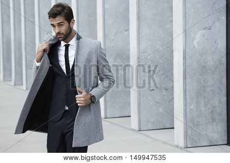 Smooth businessman in coat looking away on location