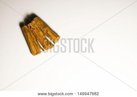 Three sticks of cinnamon in a white background