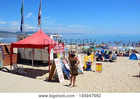 LYME REGIS, UNITED KINGDOM - JULY 18, 2016 - Holidaymakers relaxing on the beach with a deckchair and parasol rental tent in the foreground and the sea to the rear Lyme Regis Dorset England UK Western Europe, July 18, 2016.