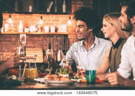 Dinner party with friends. Cheerful young people enjoying meal while sitting at the dinning table on the kitchen together
