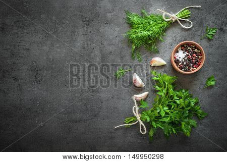 Herbs and spices at dark slate table. Parsley dill garlic and pepper. Ingredients for cooking.