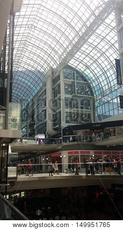 Toronto Canada - August 10 2016: Unidentified shoppers in the inside view of the Eaton Centre. A modern shopping mall in Toronto full of shoppers shops restaurant and people as editorial (Picture taken by mobilephone)