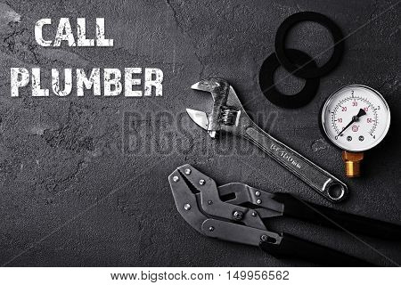 Call Plumber. Plumber tools on concrete structure background