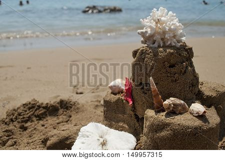 Sandcastle with starfish, coral and seashell on sandy beach, holiday concept