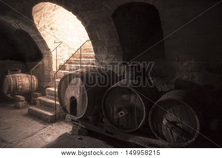 Old wine cellar with wooden barrels and stone stairs - Aged wine cellar interior with old wooden barrels and stone stairs with strong light coming down through the entrance.