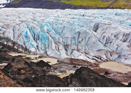 Skaftafell National Park.  Blue ice covered ground black volcanic ash. The southern part of the huge Vatnajokull glacier