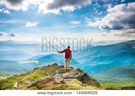 Young Man On Mountain Taking Selfie