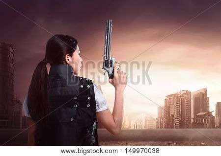 Back view of sexy asian woman using police uniform with gun on the rooftop of building